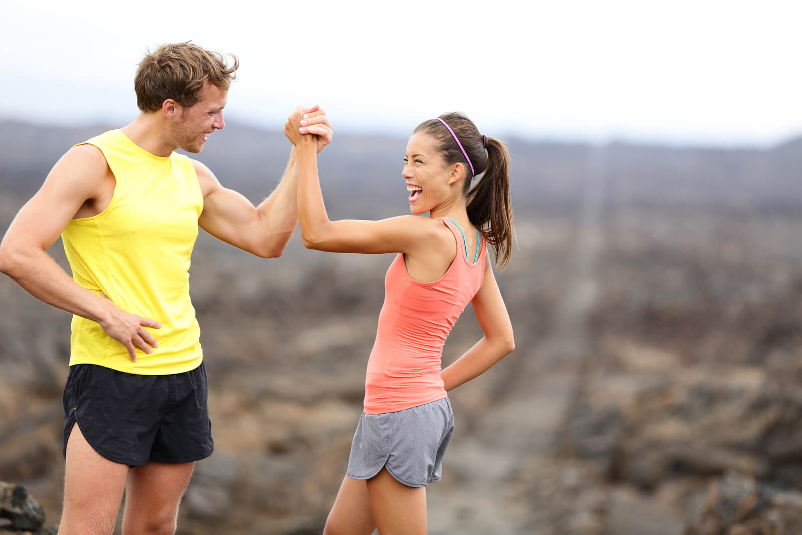 Fitness sport running couple celebrating cheerful and happy giving high five